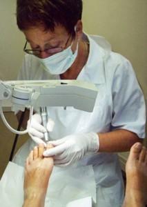 Fotobeschrijving: Voeten, handen, lamp, mondkapje, handschoenen, medisch pedicure Netty Huytker